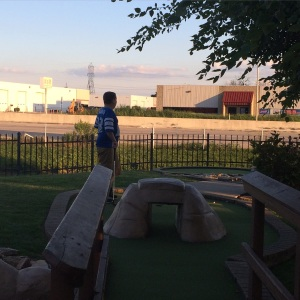 Ryan stares off into the distance while playing mini golf.